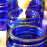 Filling the Herpes Healing Salve cobalt blue glass jars